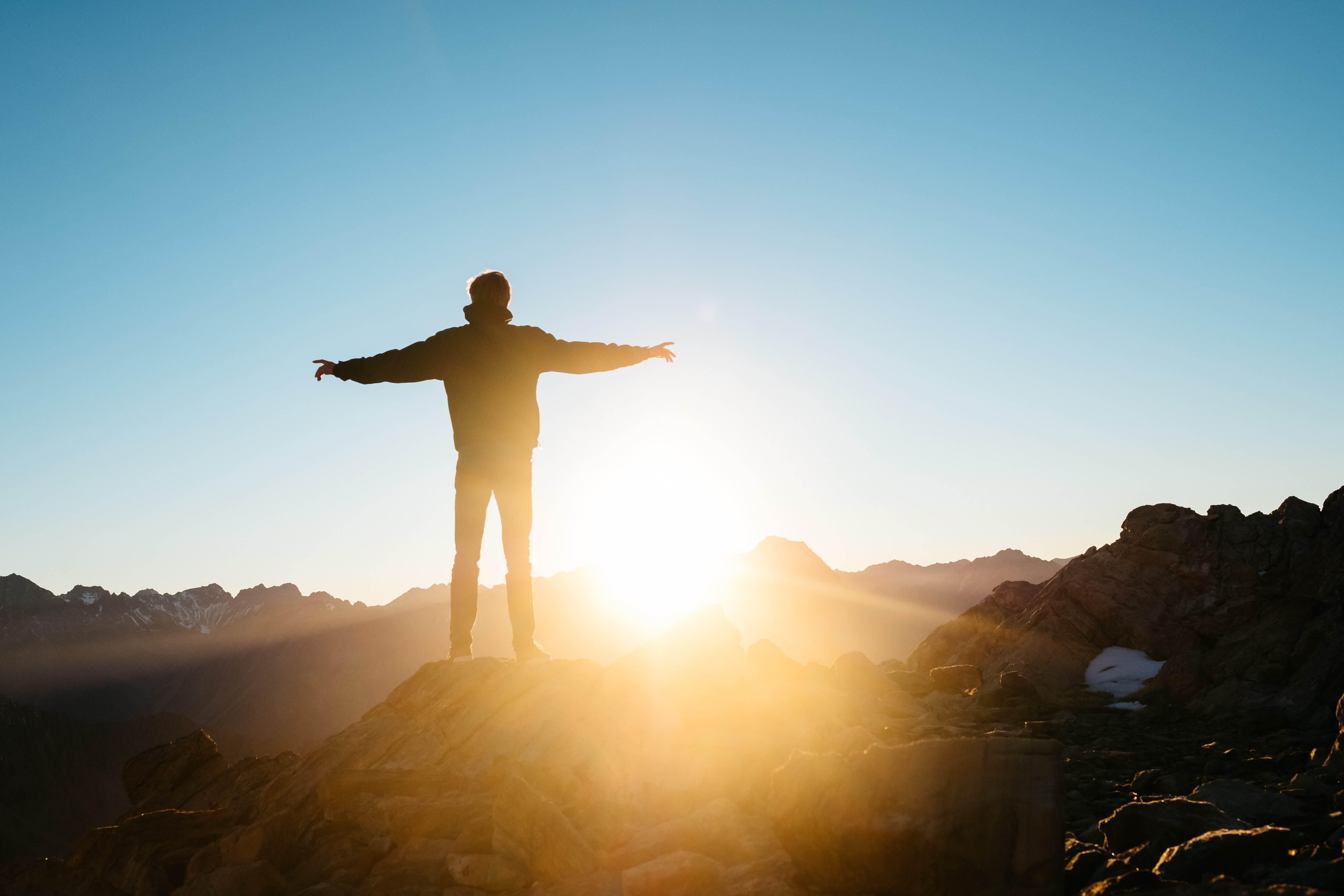 Un homme, les bras ouvert sur le col d'une montagne faisant face à un lever de soleil. Photo by @hsfju